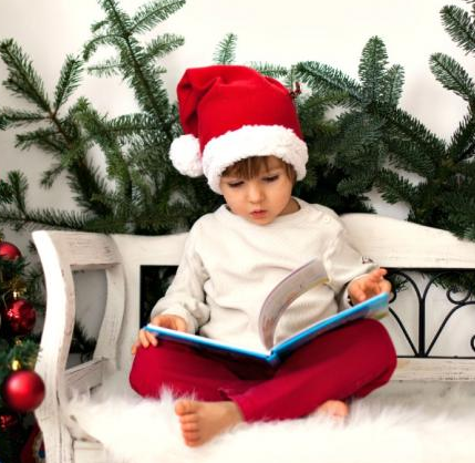 Boy wearing a Christmas hat reading a book on a bench