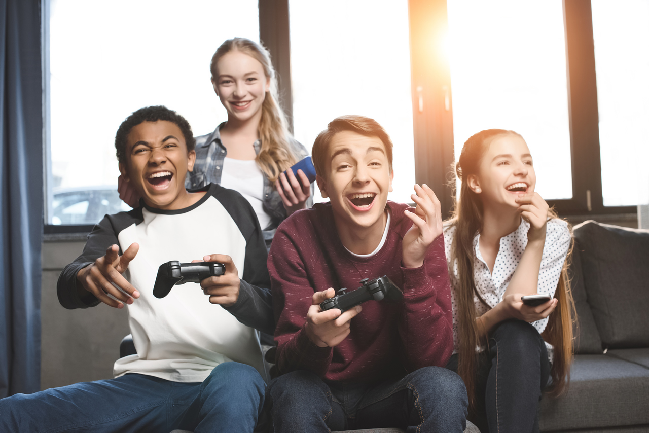 four teens playing video games